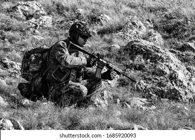 Soldier in a mountain setting. full gear with backpack holding a rifle, scouting. soldier concept. black and white with no noise and high contrast