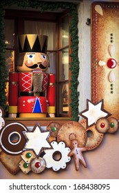 Soldier nutcracker statue standing in front of decorated Christmas window