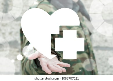 Soldier offers heart with medical cross icon on a virtual interface. Military Security and Protection Civilians. Military Hospital. Soldiers and People Health Care Safety.