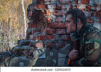 soldier on brick wall background.soldier watching the situation.soldiers waiting in ambush, close-up photo. military training camp.Kalashnikov assault rifle. AKS-74