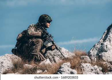 Soldier on a hillside. crouching in full gear with backpack. soldier concept