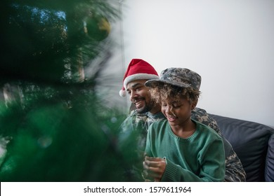 Soldier on military leave decorating Christmas tree and enjoying holidays with his daughter.