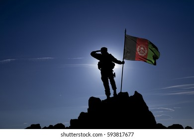Soldier on top of the mountain with the Afghan flag