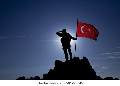 soldier on top of a mountain with a Turkish flag