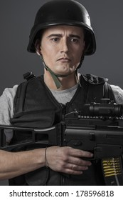 Soldier, paintball sport player wearing protective helmet aiming pistol ,black armor and machine gun