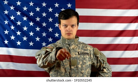 The soldier points a finger at the camera. Portrait of an American soldier with a serious look on the background of the national flag