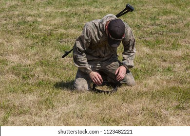 The soldier prays sitting on a grass