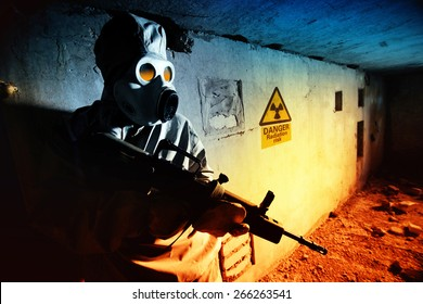 Soldier in protective clothes and mask with the rifle on the ruined bunker background.