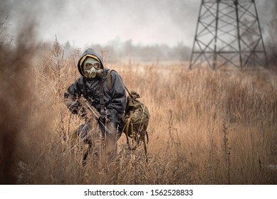 Soldier with rifle in raincoat and gas mask is walking outdoor.