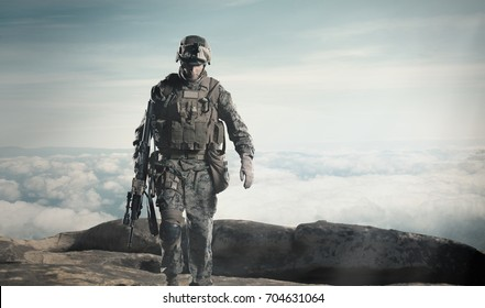 soldier with a rifle. Steps against clouds.
