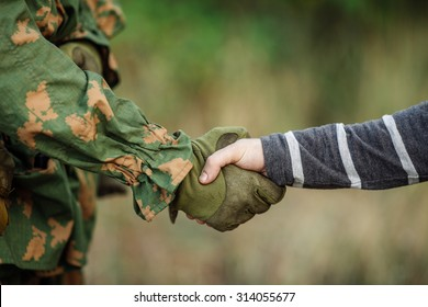 Soldier shaking hands with civil man on outdoor background