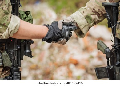 Soldier shaking hands on outdoor background