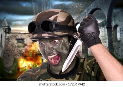 soldier showing a knife  in a combat zone