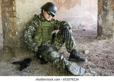 The soldier sits leaning against a wall in a ruined building. Military conflicts