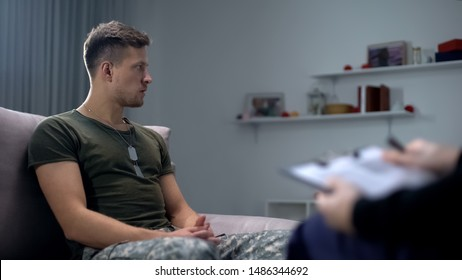 Soldier sitting on sofa during psychological therapy, suffering ptsd or dementia
