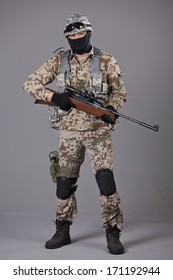 Soldier with sniper rifle posing over grey background