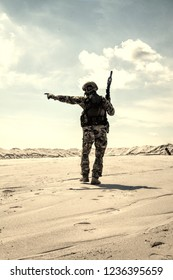 Soldier of special forces, infantry rifleman in military ammunition walking in desert and pointing on horizon. Military reconnaissance team leader managing dead ground observation with combat patrol