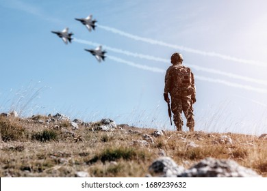 Soldier standing on a mountain looking at a shadow of a blury war planes passing overhead. Freedom. soldier concept
