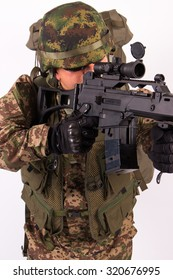 Soldier with sunglasses, military backpack and trigger on white background