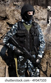 Soldier of Ukraine Army guarding borders with automatic AK 74 rifle wearing heavy ammunition. National Guard officer on duty. Vest, black mask and camouflage clothing.