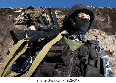 Soldier of Ukraine National Army in full ammunition holding rifle on his shoulder guarding borders. National Guard officer on duty. Heavy armored warrior in helmet and mask