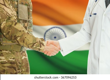 Soldier in uniform and doctor shaking hands with national flag on background - India