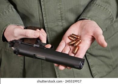 Soldier in uniform holding a gun Colt cartridges to it