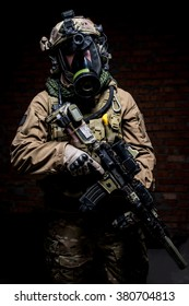 Soldier in uniform and respirator standing on dark background with rifle/Spec ops soldier in uniform with assault rifle