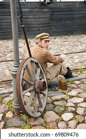 Soldier in uniform of World War I, sit down, resting on the pavement and smoking. Costume accord the times of World War I. Photo made at cinema city Cinevilla in Latvia.