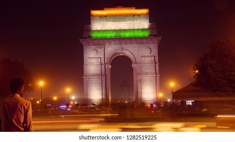 A soldier watching India Gate at night, while the vehicles are passing by. Long exposure view of India Gate at New Delhi, which is pride of Indians.