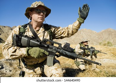 Soldier with weapon signaling during a battle