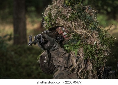 Soldier wearing camouflage, in wood, aiming with sub machine gun