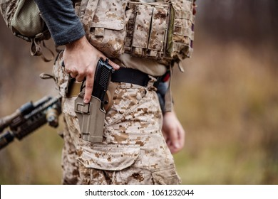 Soldier wearing uniform with gun in hand,keep gun in the holster. military concept