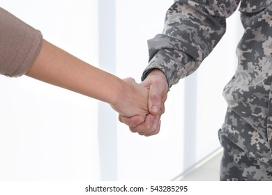 Soldier and young woman holding hands on light background, close up