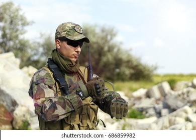 Soldiers airsoft preparing for the job wearing gloves, toned
