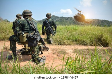 Soldiers boarding a military helicopter , Soldiers preparing running through a sandstorm,copy space.