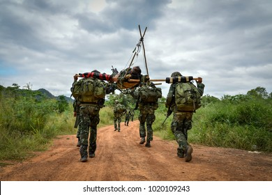 Soldiers are carrying their wounded soldiers on the battlefield to safe places for medical treatment.