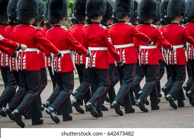 Soldiers in classic red coats march along The Mall in London, England in a grand Trooping the Colour spectacle of the Queen's Royal Guard