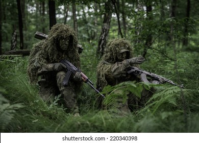 Soldiers dressed in ghillie camouflage on nature.