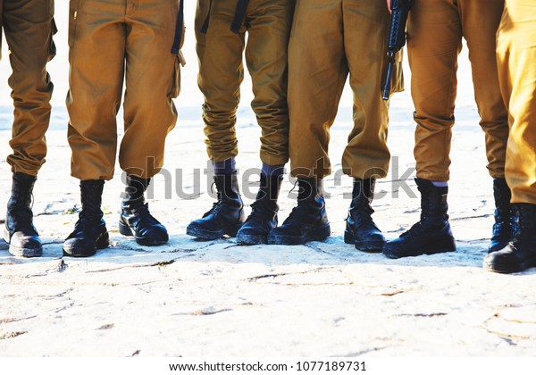 The soldier's footwear of the Israeli army which is put on legs in clear sunny day