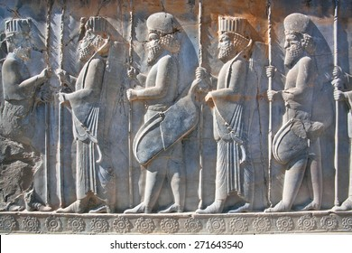 Soldiers of historical empire with weapon in hands. Stone bas-relief in ancient city Persepolis, Iran. Capital of the Achaemenid Empire (550 - 330 BC). UNESCO declared Persepolis a World Heritage Site