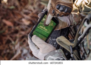 soldiers holding gps in hand and determines the location of coordinates. militaryand technology concept
