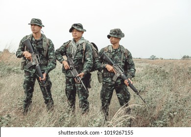 Soldiers holding weapon. Chinese male soldiers holding rifles. Field combat and counter terrorist training exercise. Special force army ranger team.