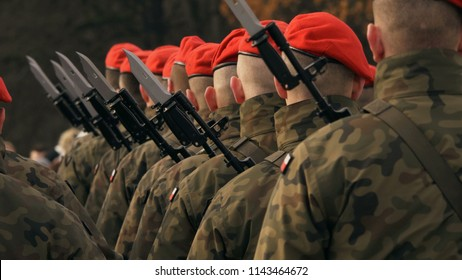 soldiers with machine guns and bayonet knives stand in a row, in red berets