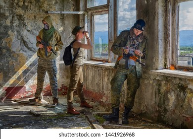 Soldiers or mercenaries (two man and one girl in military clothes)  with weapon (macchine guns) follow the perimeter by binoculars inside of ruined building