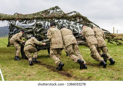 Soldiers from the Royal Artillery Corp push a 105mm Light Gun into position underneath camouflage netting