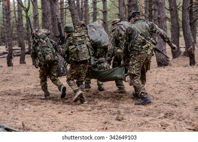 Soldiers run away from the battlefield with stretcher and wounded soldier