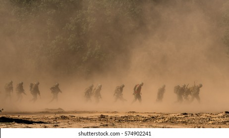Soldiers running through a sandstorm.