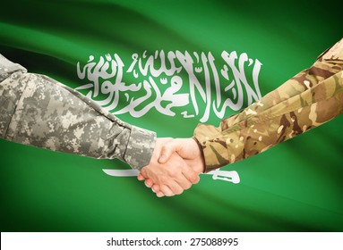 Soldiers shaking hands with flag on background - Saudi Arabia