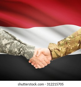 Soldiers shaking hands with flag on background - Yemen
